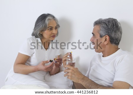 Wife giving medication to husband