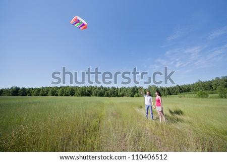Wife, husband launch kite in field near wood - stock photo