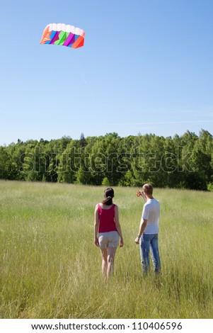 Wife, husband launch kite in field near wood, back - stock photo
