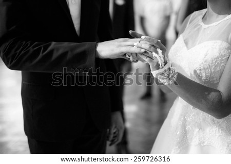 Wife  put a ring on finger of his lovely groom. - stock photo