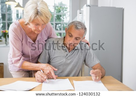 Wife showing where to sign to her husband in the kitchen - stock photo