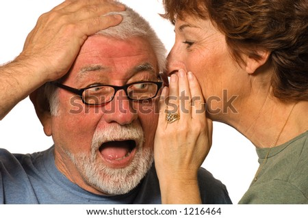 Wife whispers into husband's ear, surprising him - stock photo