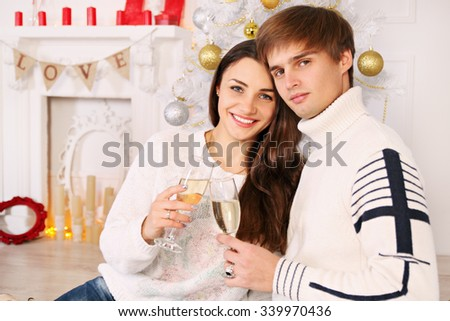 wife with her husband sitting by the Christmas tree - stock photo