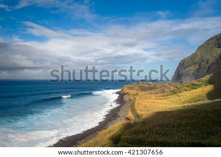 Wild bay Calhau das Achadas aka The Bay of Discoverers landscape with calm ocean waves, fields lit by sun and steep mountains. Madeira island, Portugal. - stock photo