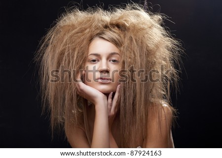Wild beautiful girl portrait with shaggy hair on a black background posing - stock photo