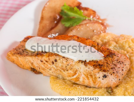 Wild-caught Salmon Steak on bed of cheese grits with pears candied in honey wine and cinnamon sugar sauce. Selective focus with shallow depth of field. - stock photo
