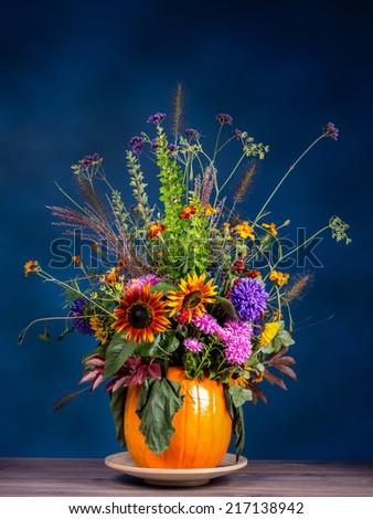 Wild flowers bouquet in carved pumpkin vase over dark blue background - stock photo