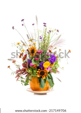 Wild flowers bouquet in carved pumpkin vase over white background - stock photo
