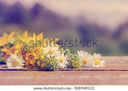 Wild flowers on old wooden table. The background for the text. Tone correction in retro style. - stock photo