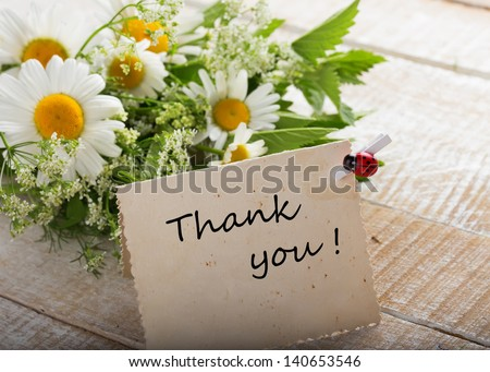 Wild flowers on wooden background with vintage card and word thank you written on it. Selective focus. - stock photo