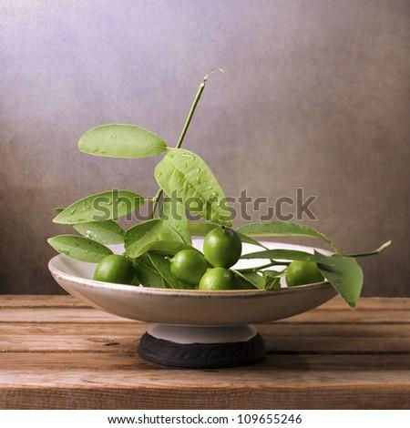 Wild green lemons in vintage bowl - stock photo