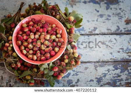 Wild strawberry in a bowl on a background of old boards - stock photo