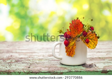 Wild strawberry in a cup over the wooden table, soft green bokeh background  - stock photo