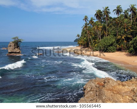 Wild tropical beach with lush vegetation and rocky islet, Costa Rica, Manzanillo, Central America