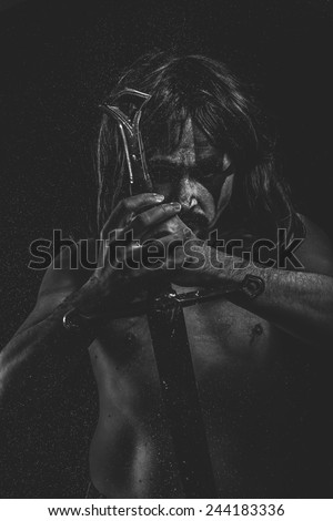 Wild Warrior with huge metal sword - stock photo