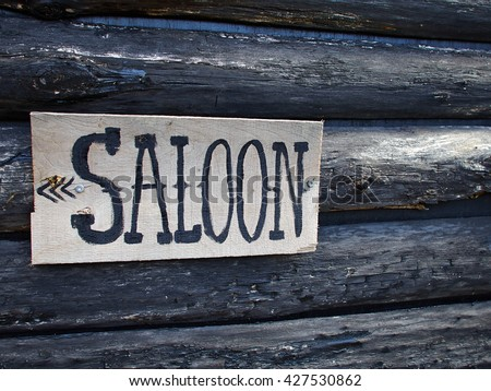 Wild west American saloon sign hanged on a wooden house    - stock photo