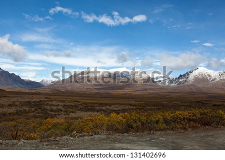 Wilderness of Alaska tundra in late fall with snow on mountains - stock photo