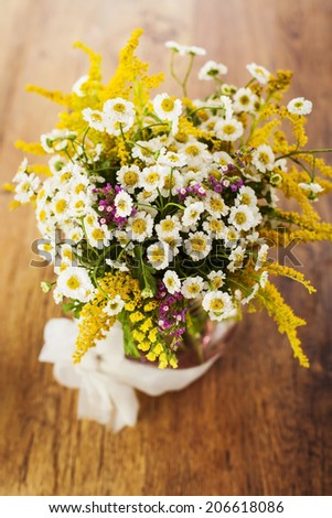 Wildflowers bouquet in glass vase on wooden background - stock photo