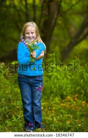 Wildflowers presented by girl in blue in a green forest - stock photo