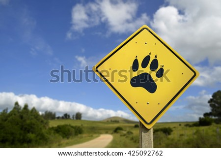 Wildlife animal conservation, save wild species concept. Road sign with paw foot print icon in wilderness environment, includes copy space. - stock photo