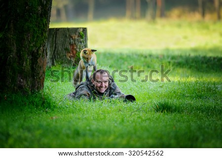 Wildlife photographer hidden in grass with big smile in face, having curious fox on his back looking down to the photographer - stock photo