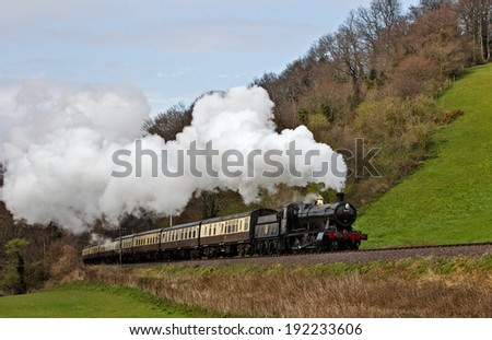 WILITON, UK - MARCH 28: A preserved steam locomotive passes along the bottom of Castle Hill with a passenger train during the WSR spring steam gala on March 28, 2014 in Wiliton - stock photo