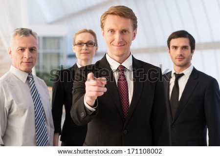 Will you join our team? Confident young man in formalwear pointing you and smiling while his colleagues standing behind him - stock photo