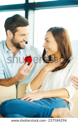 Will you marry me? Handsome young man making a proposal while giving an engagement ring to his girlfriend  - stock photo