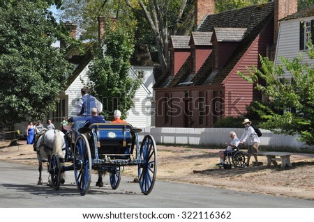 WILLIAMSBURG, VA - SEP 6: Horse-drawn carriage rides in Williamsburg, Virginia, on Sep 6, 2015. Colonial Williamsburg is a living-history museum with exhibits of restored or re-created buildings. - stock photo