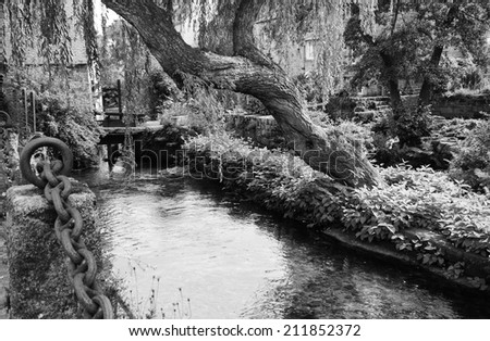 Willow tree over the idyllic canal in Pont-Aven. Brrittany, France. Retro aged photo. Black and white.