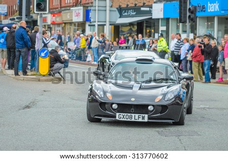 Wilmslow UK - July 9, 2013 : A Lotus Elise drives sideways during the annual public gathering of local sports and super cars in affluent Wilmslow, Cheshire - stock photo