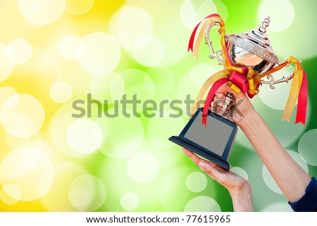 win award cup in hand - stock photo
