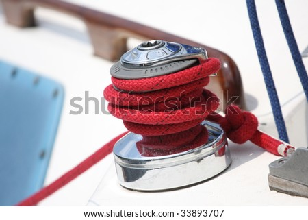 Winch and red rope on a sailboat - stock photo