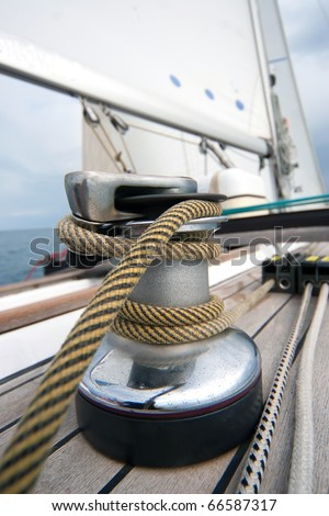 Winch with rope on sailing boat in the sea - stock photo