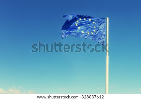 Wind blown European union flag and blue sky background - stock photo