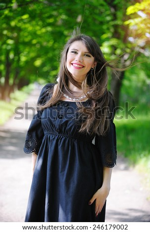 wind blows her hair woman in the park. - stock photo