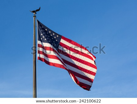 Wind blows the USA flag of stars and stripes with eagle flagpole against blue sky late in the afternoon as sun sets - stock photo