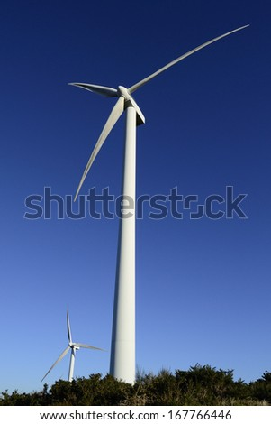 Wind energy business. Wind turbine closeup with blue sky and green grass - stock photo