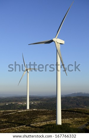 Wind energy business. Wind turbine closeup with blue sky, green grass and village