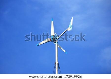 Wind energy turbine on blue sky - stock photo