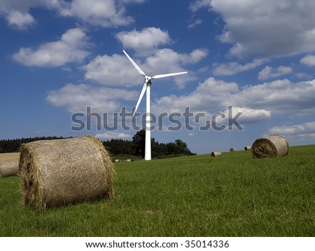 Wind Farm against blue sky with white clouds and bale of straw on the ground - stock photo