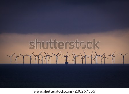 Wind farm in sunset. Clean energy for the future. - stock photo