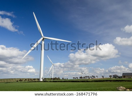 Wind Farm - Wind turbines in field with blue sky and clouds behind. - stock photo