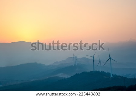 wind farm with distant mountains silhouette at sunset