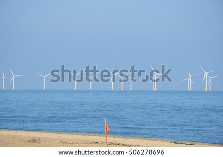 Wind farm with sandy beach and lifebelt  in foreground