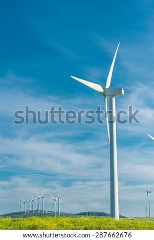 wind generator in a field on beautiful blue sky background - stock photo