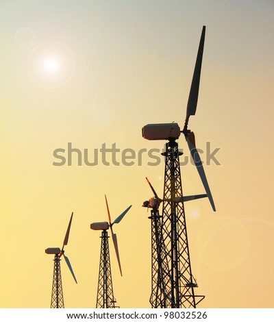 Wind generator on the background of the sunset sky - stock photo