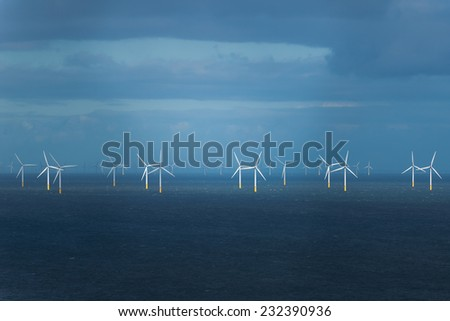 Wind generators in Irish sea, during rain and storm. - stock photo
