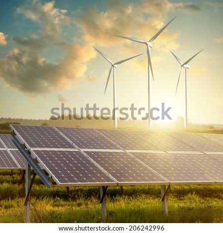 Wind generators turbines and solar panels on sunset summer landscape - stock photo
