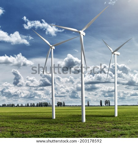 Wind generators turbines on summer landscape under blue sky and clouds